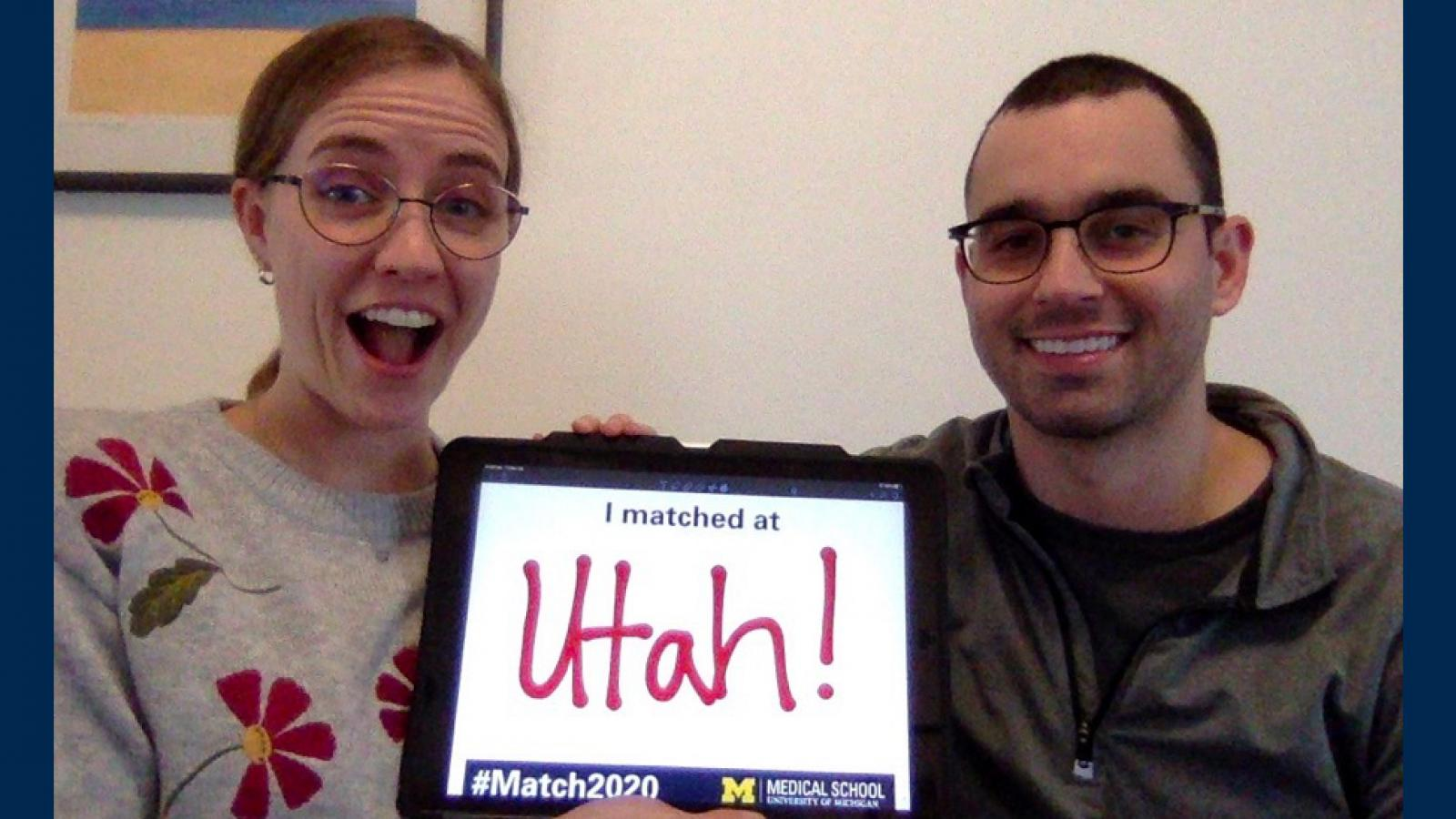 "Couple on a couch one with a surprised expression holding a sign that reads ""I matched at Utah!"""