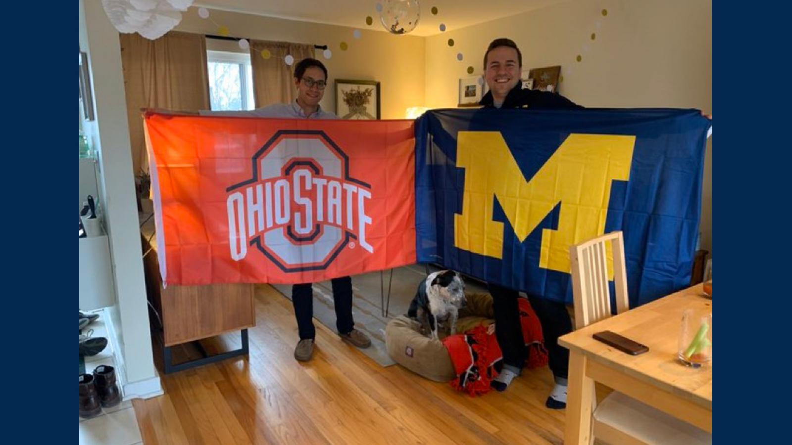 Two M4's one holding an OSU Flag the other holding a UM Flag
