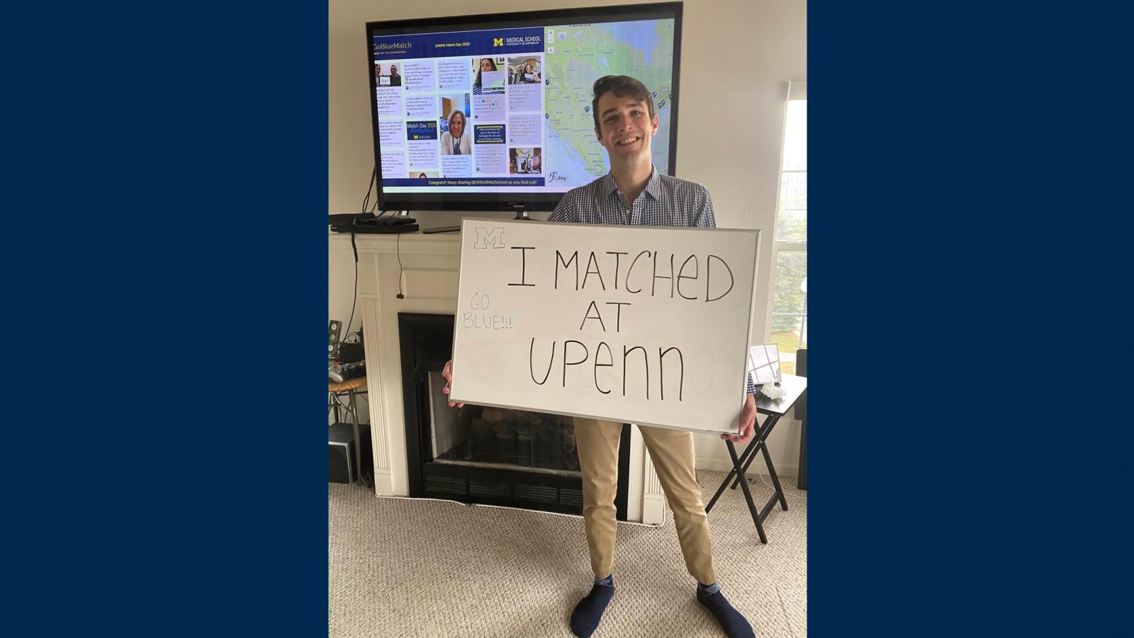 "M4 in front of a screen displaying match locations, holding a sign that says ""I matched at U Penn"""