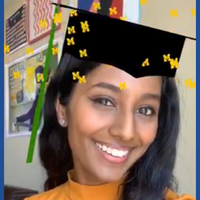 Graduate wearing virtual graduation cap with block Ms raining down