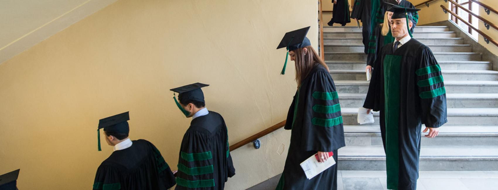 Medical students in caps and gowns walk down the hall