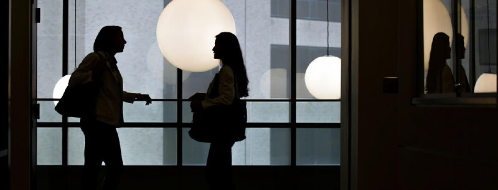 Silhouetted students talk in the Tauman Health Sciences Library