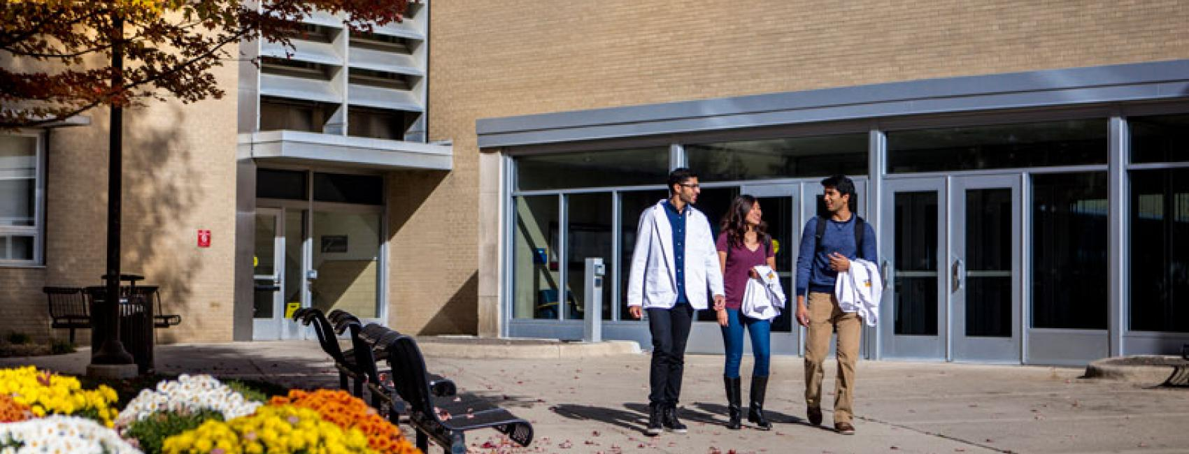Students pass the Medical Science building on a fall day