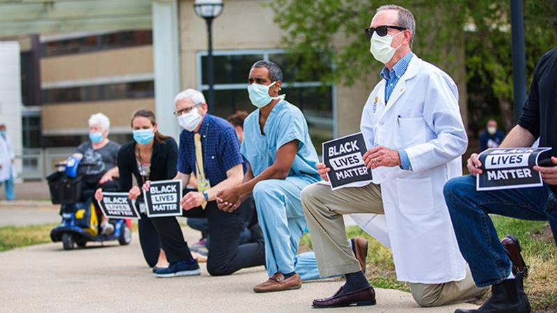 Faculty, staff, and learners kneel during the Juneteenth observance at Michigan Medicine