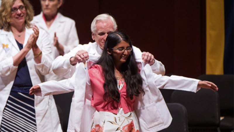 Dr. Robert Bartlett cloaks Hanna Cheriyan with her white coat