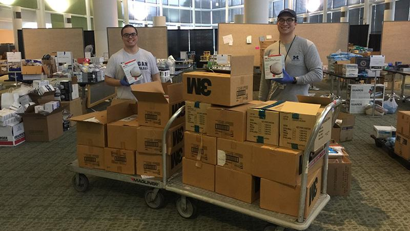 UMMS students Quintin Solano (left) and Alex Reardon help inventory donated PPE at the U-M North Campus Research Complex