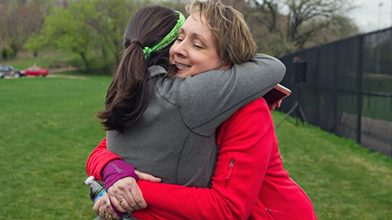 Justine Hein hugs a student at M-Home Olympics