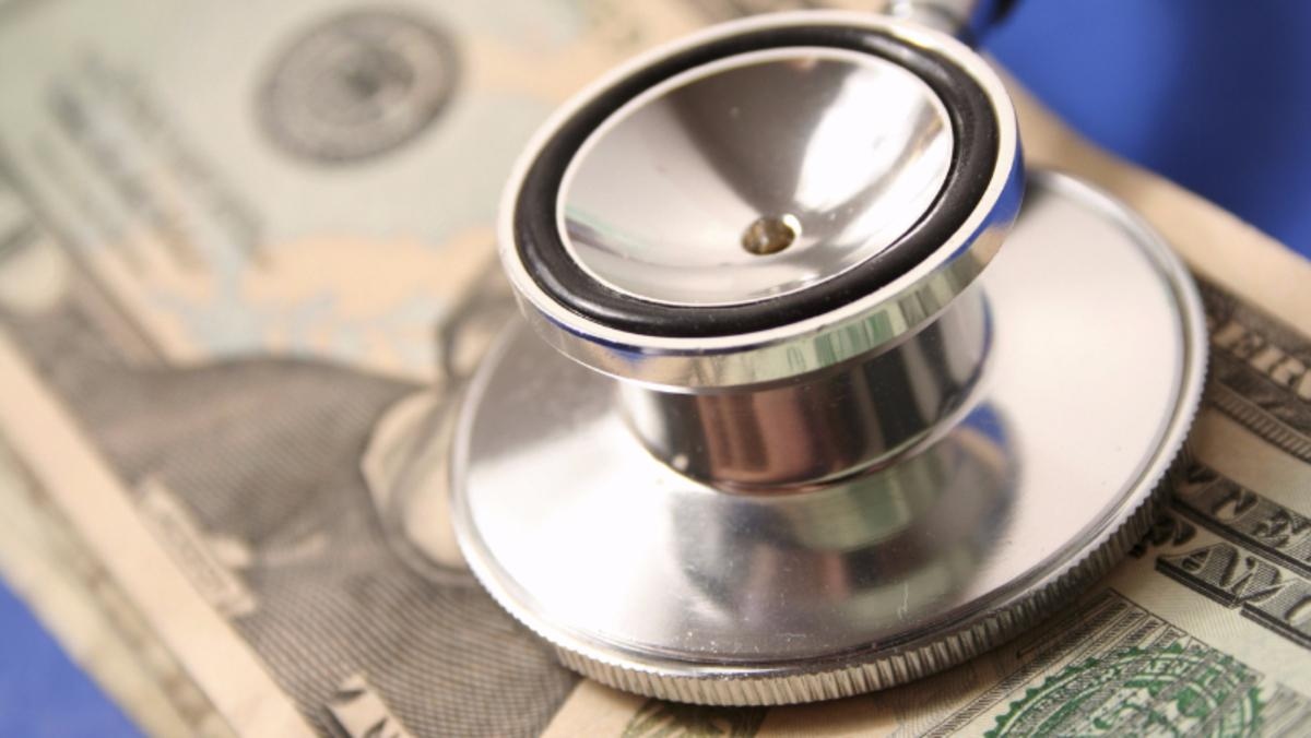 Stethoscope placed on top of money