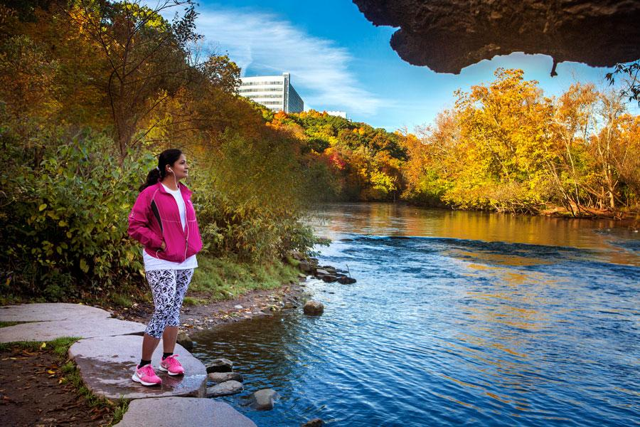 Jogger gazes at the Huron River on a fall day