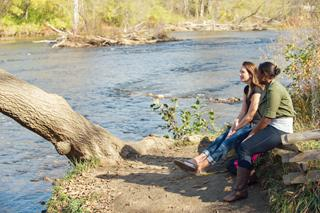 Students relax beside the Huron River