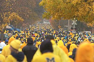A crowd dressed in maize and blue
