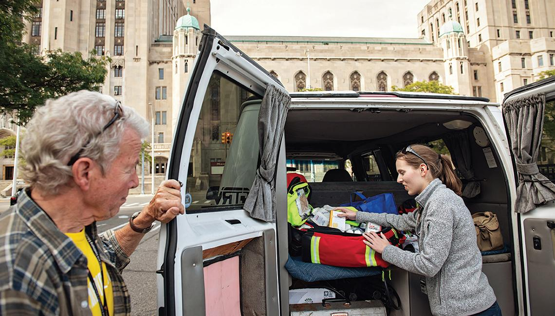 Medical student unpacks medical bag in the back of an van in downtown Detroit