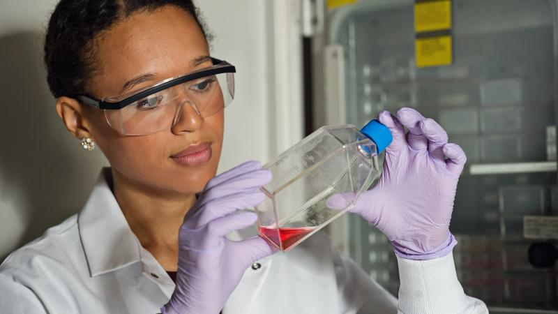 Female research student looking at bottle