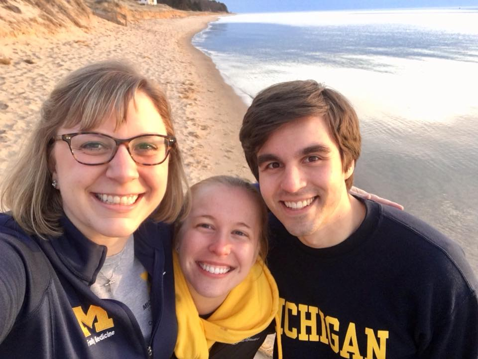 The three chief residents smiling with a sandy beach in the background.