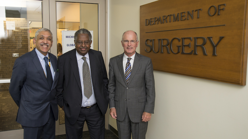 Dr. Raghavendran, Dr. Debas, and Dr. Mulholland in front of the Department of Surgery sign