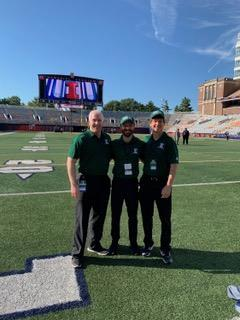 Three male physicians standing in the middle of a football field. They are each wearing dark green polo shirts.
