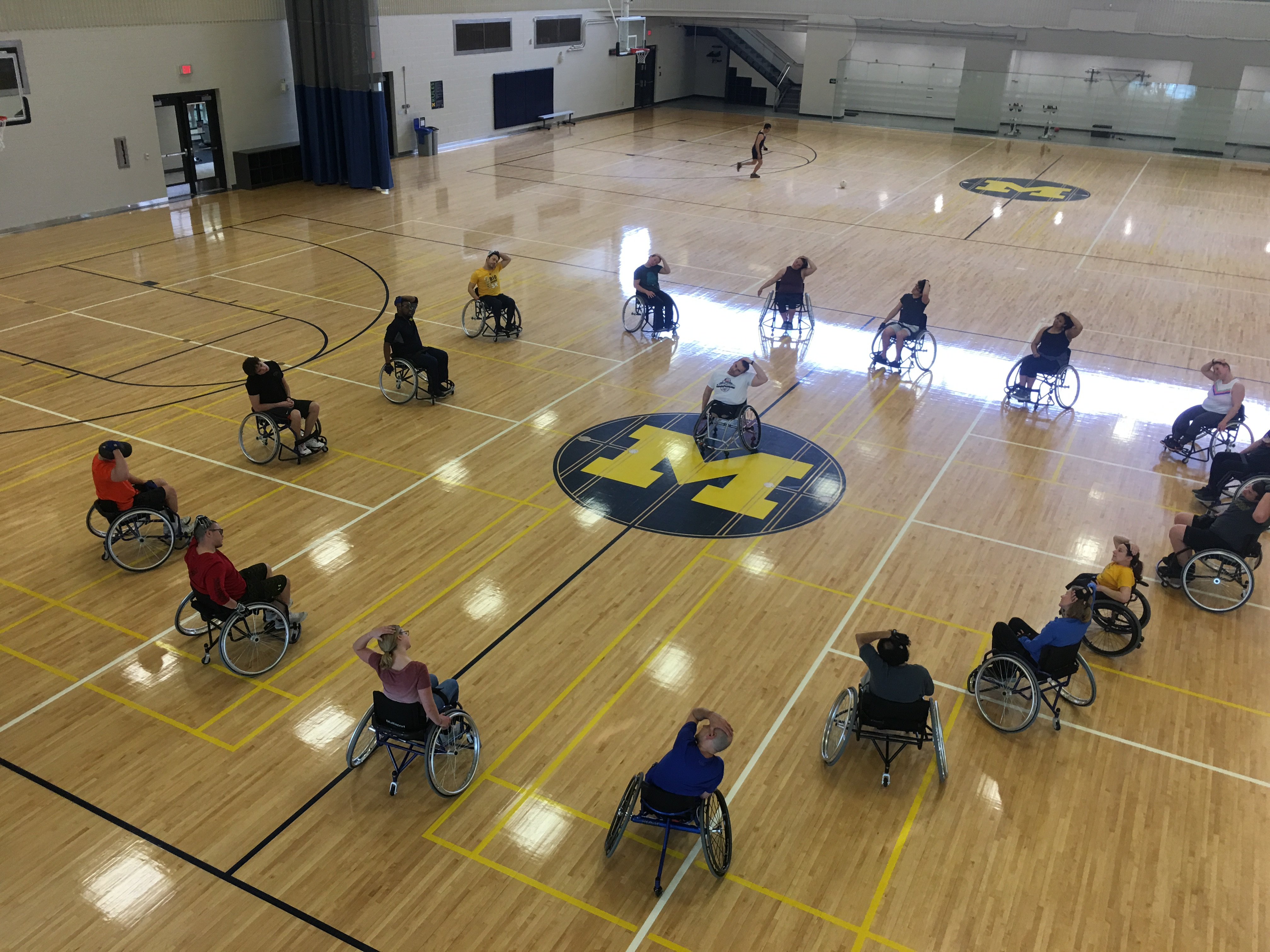 Wheelchair basketball players arranged in a circle in a U-M gym stretch before a drop-in game.