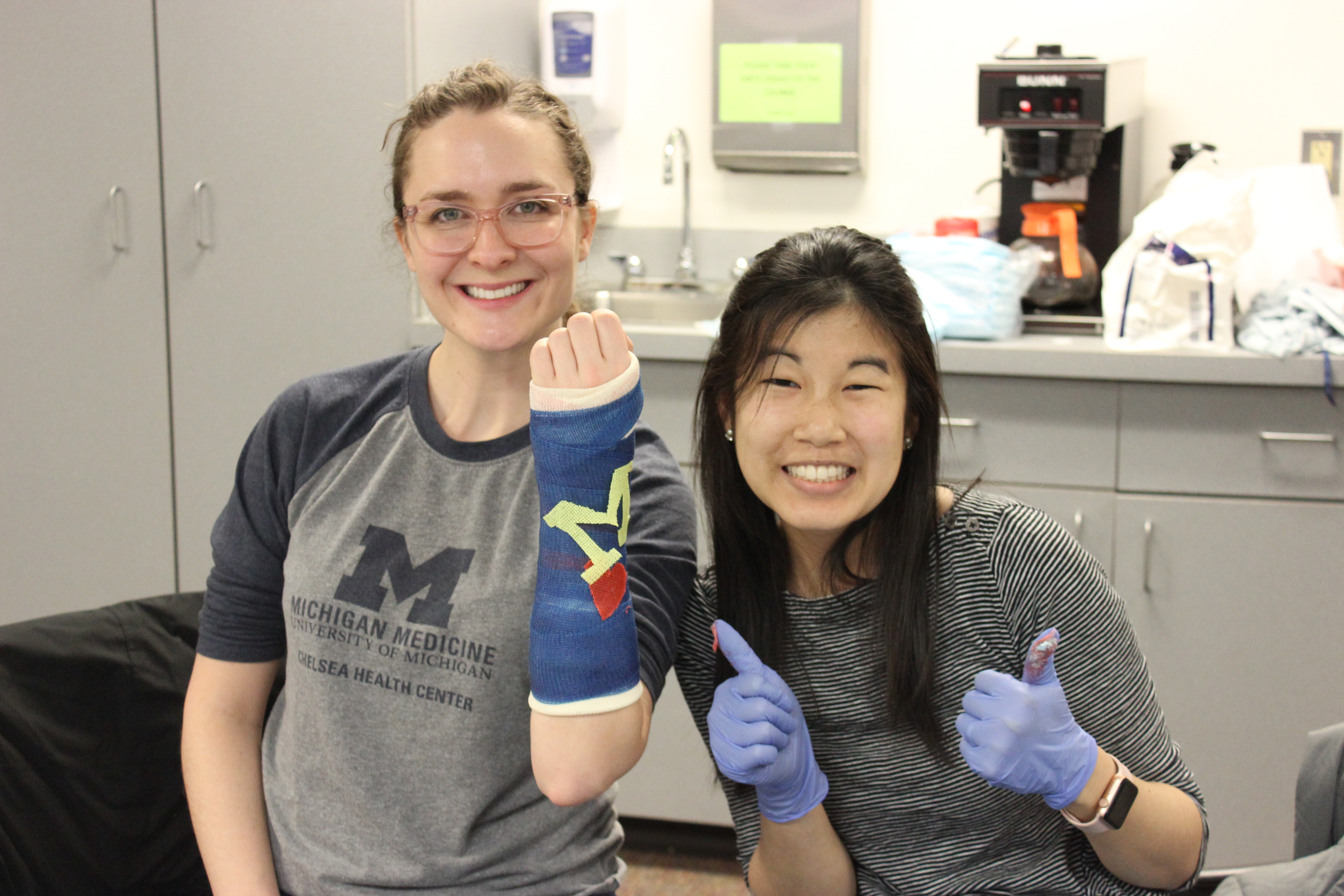 Two female residents show off a a wrist cast completed during a casting course. The case has a block M on it.