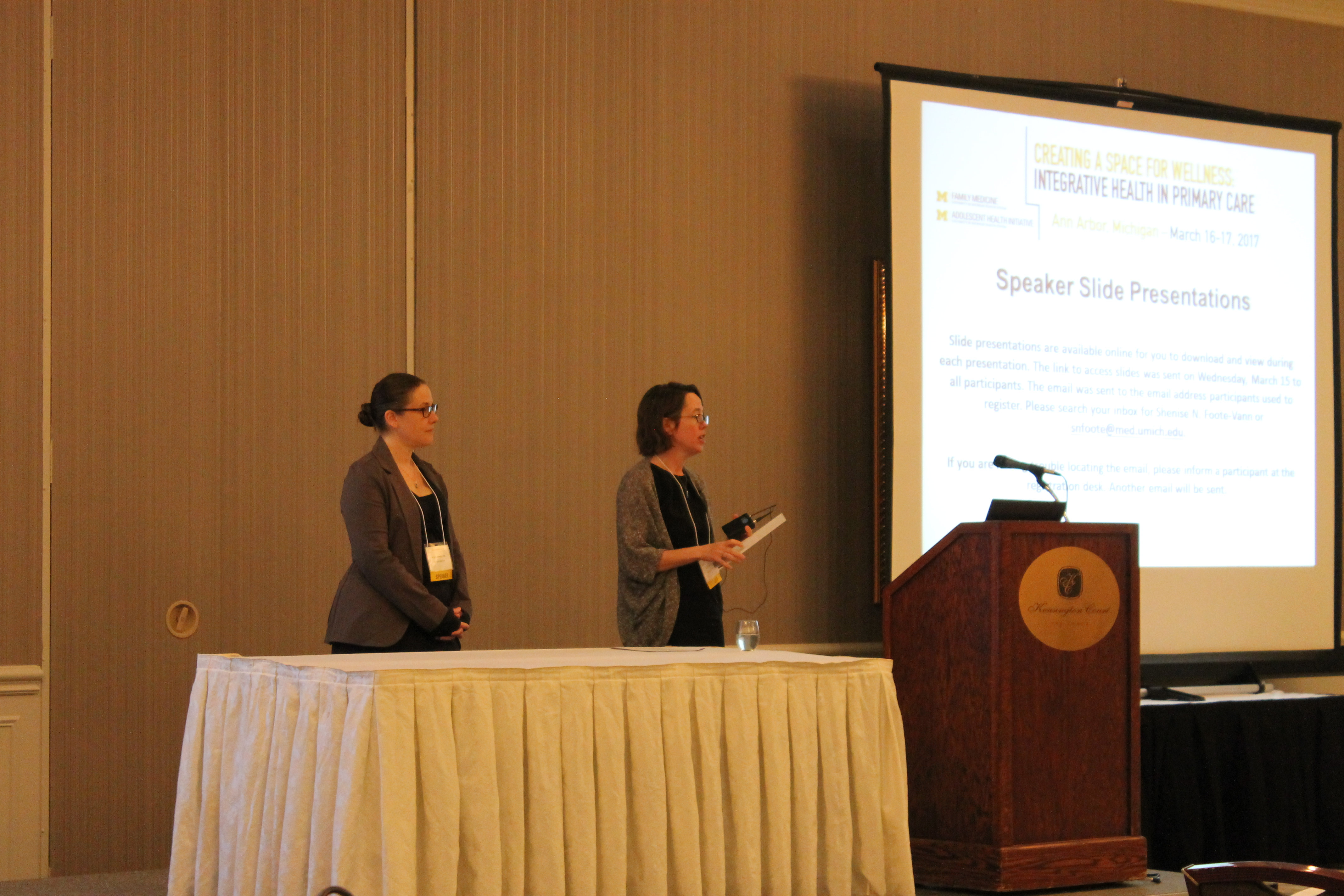 Drs. Jill Schneiderhan and Amy Locke stand on a stage in front of a screen giving a presentation.