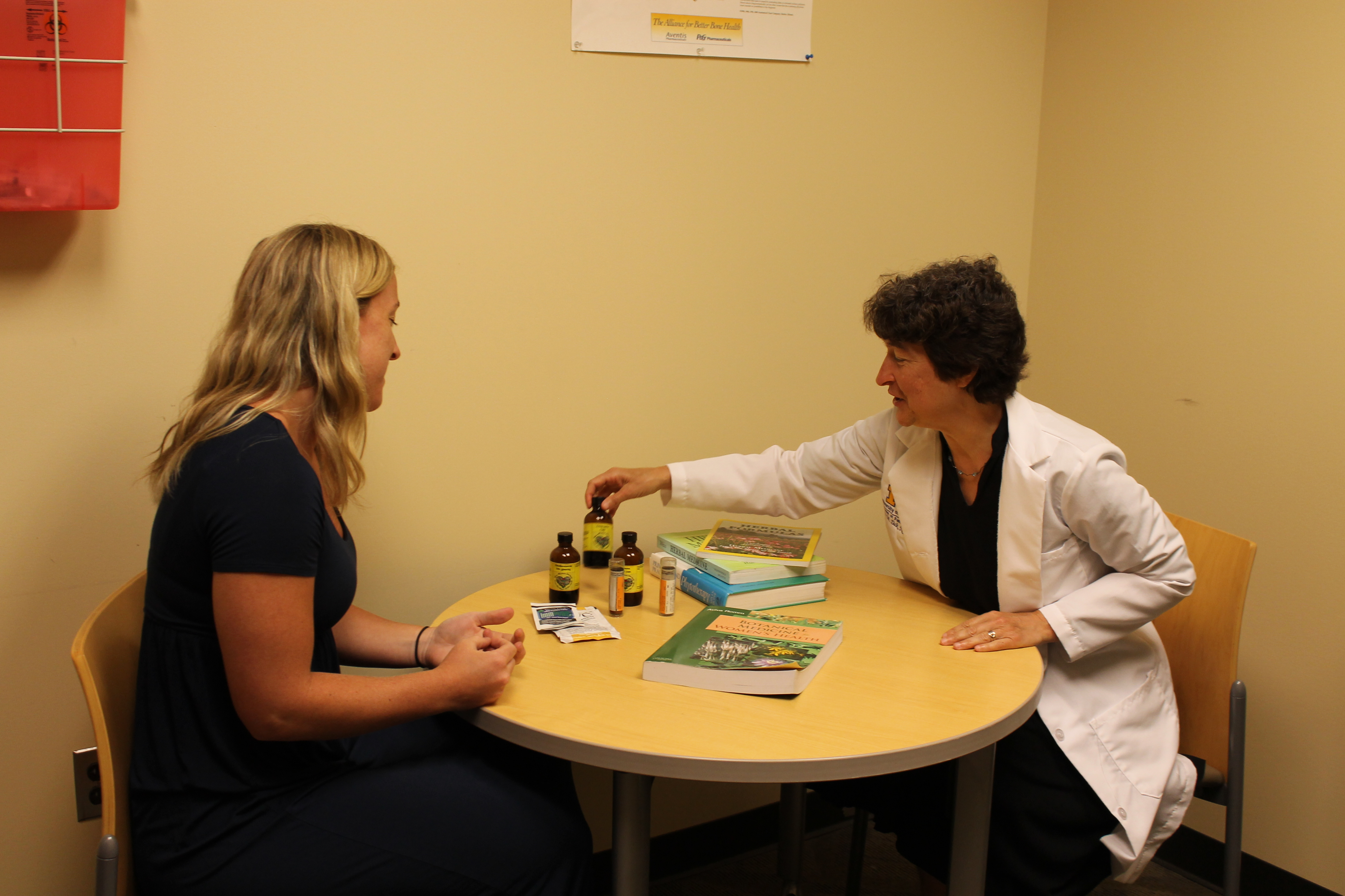Dr. Suzie Zick reviews nutrition information seated at a table with another person.