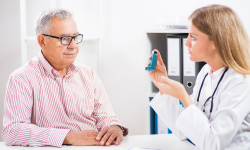 Doctor teaching patient how to use inhaler