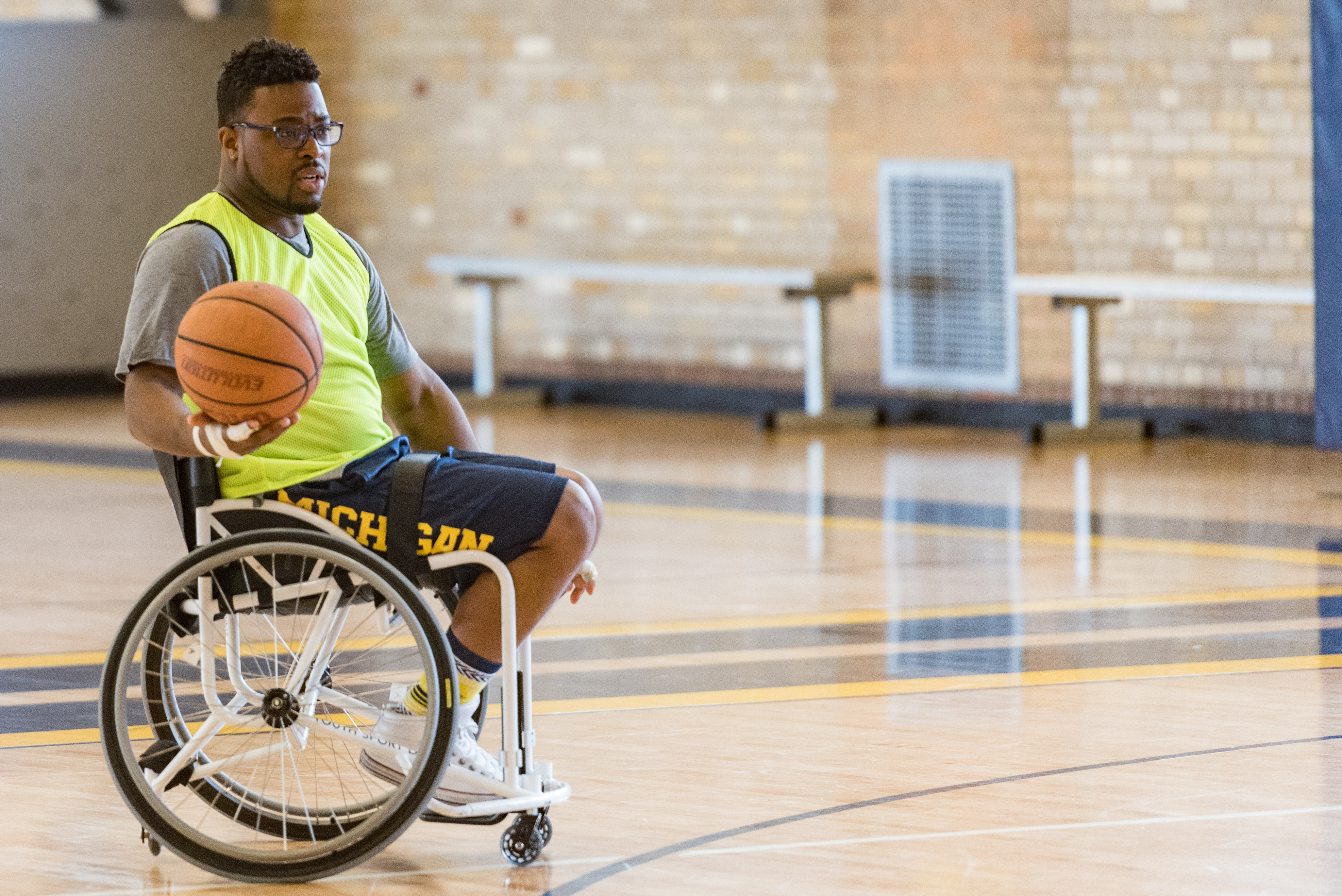 Dr. Feranmi Oklanmi sits in a sports wheel chair and holds a basketball in one hand. He is on a basketball court.