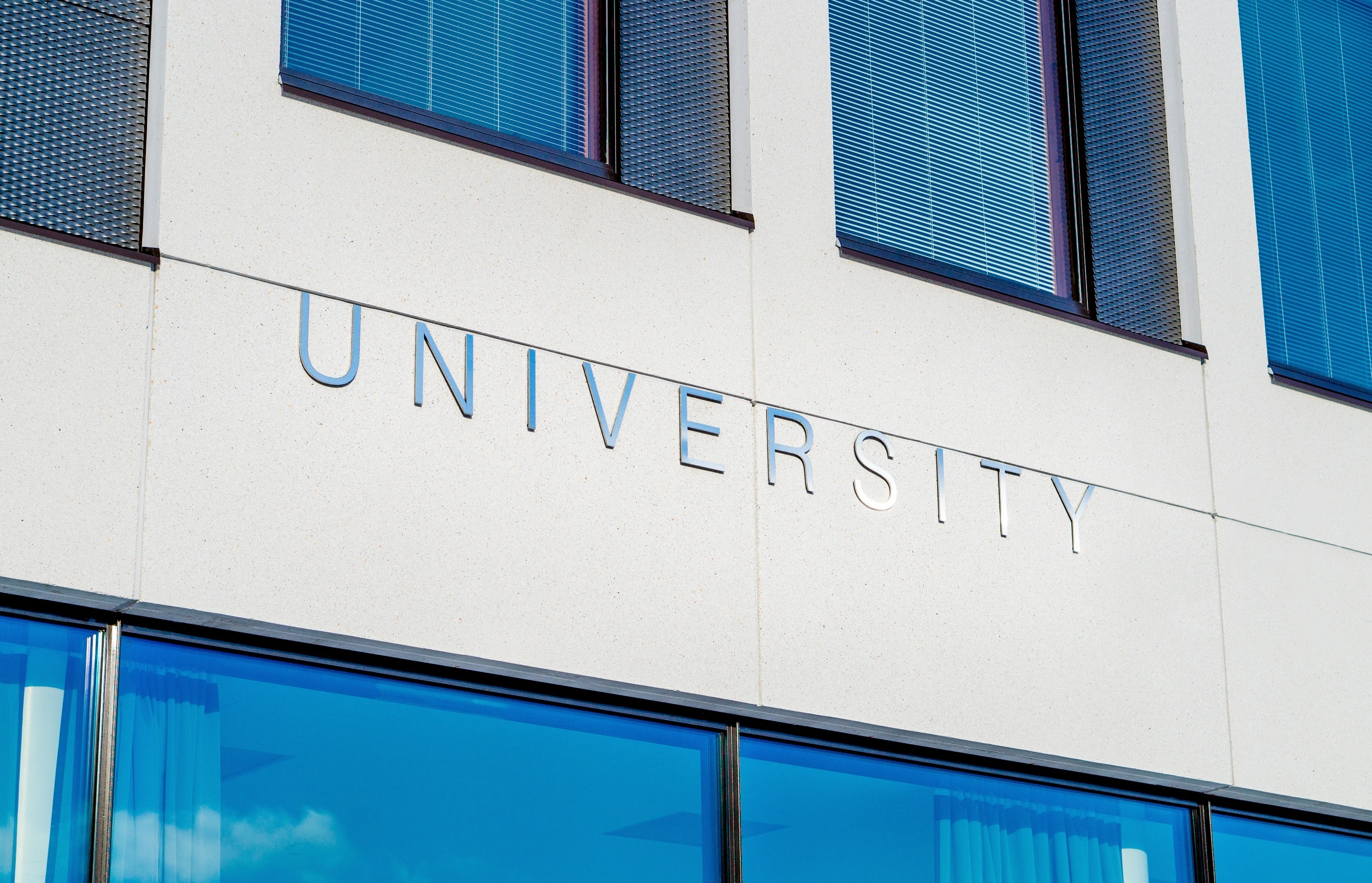 "A close up of a large building with oversized windows. The word ""University"" appears on the building."