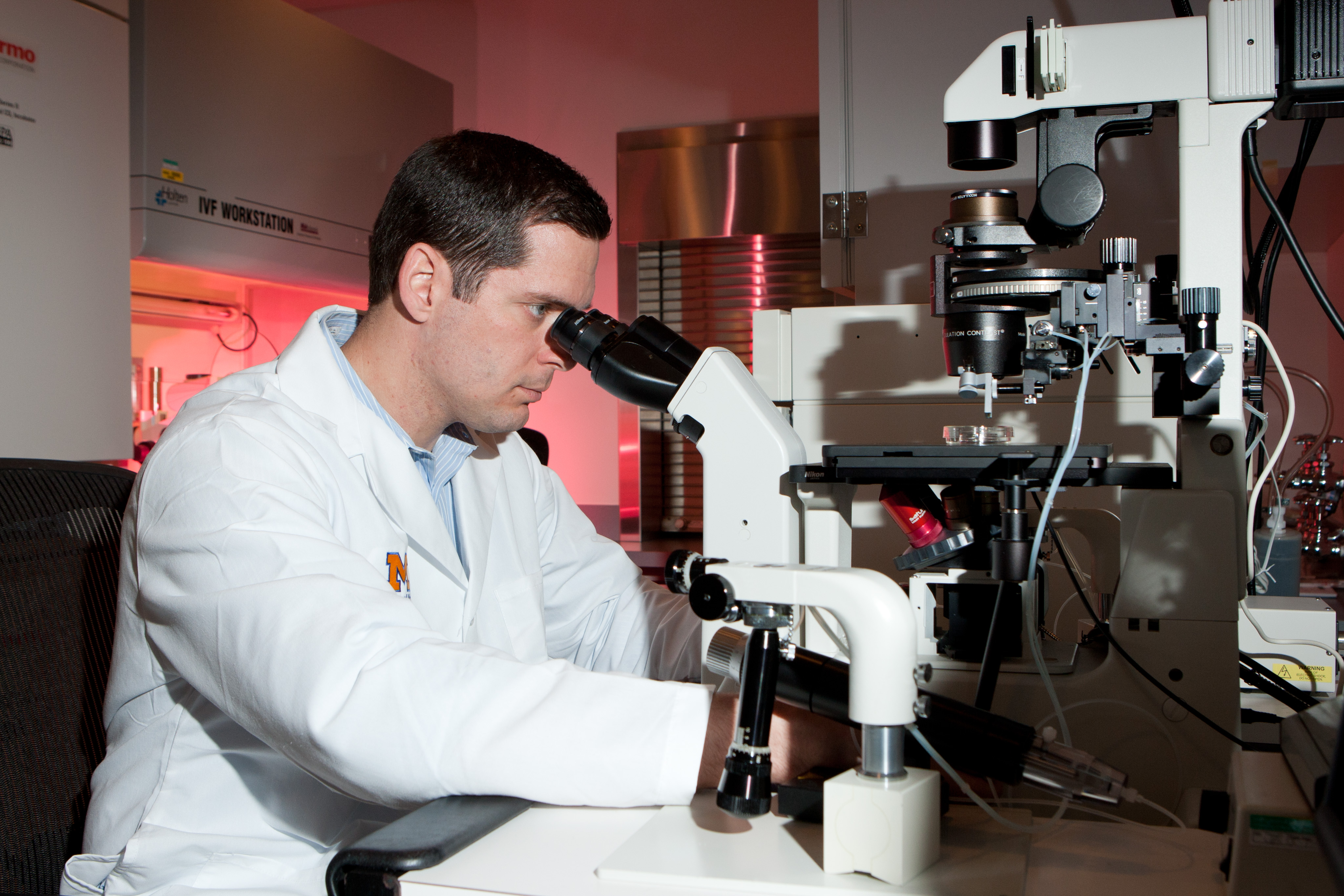 Technician looking into microscope