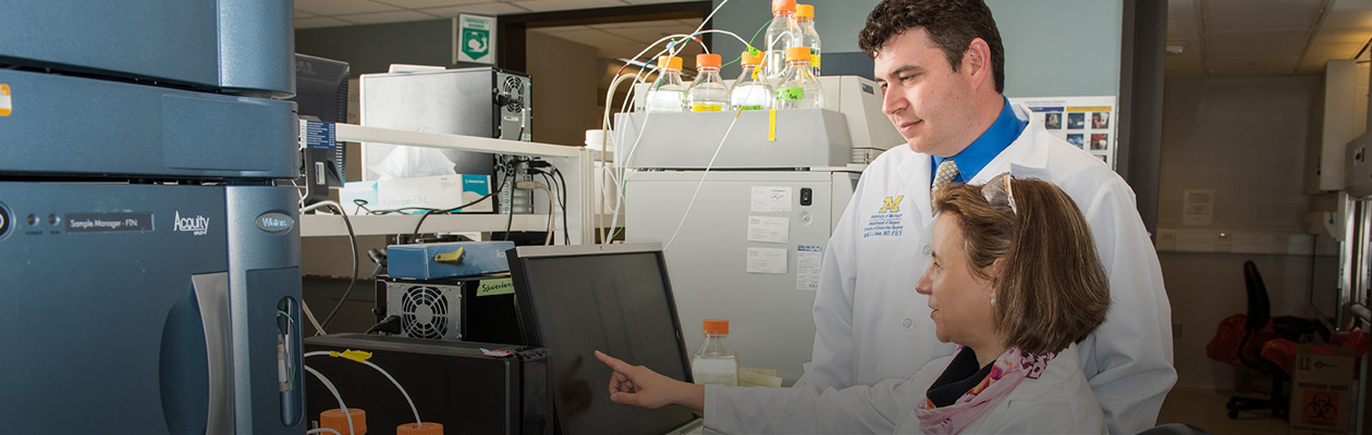 Mark Cohen and Anna Schwendeman in the lab looking at a computer