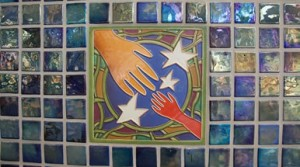 Stained glass depicting an adult hand and child hand reaching toward each other