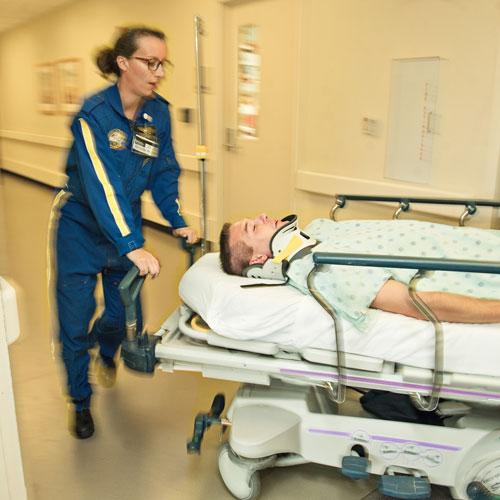 Emergency Medicine residents wheel gurney down hall