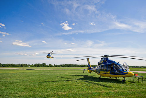 Survival Flight helicopters landing in field