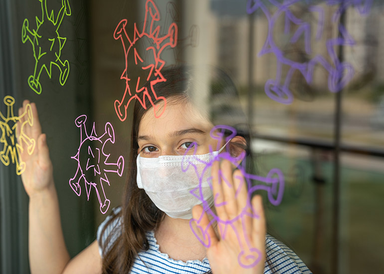 girl wearing face mask mooking out window sad, window decorated with paper coronavirus