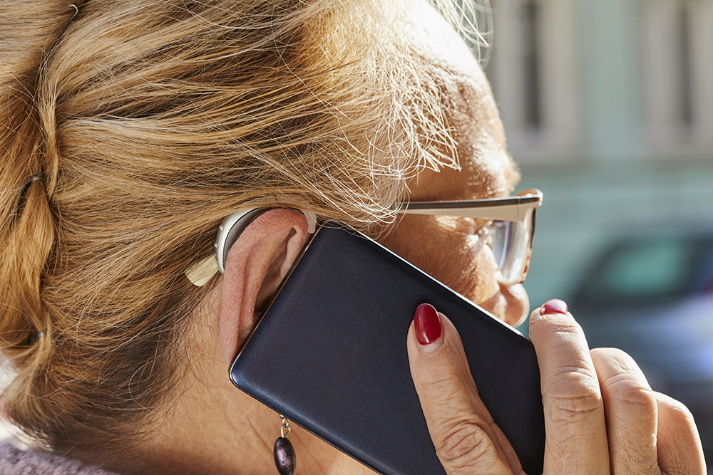older woman on cell phone wearing hearing aid