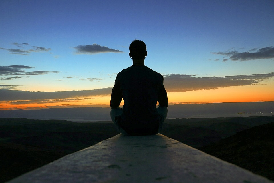 image of person sitting outside meditating at sunset