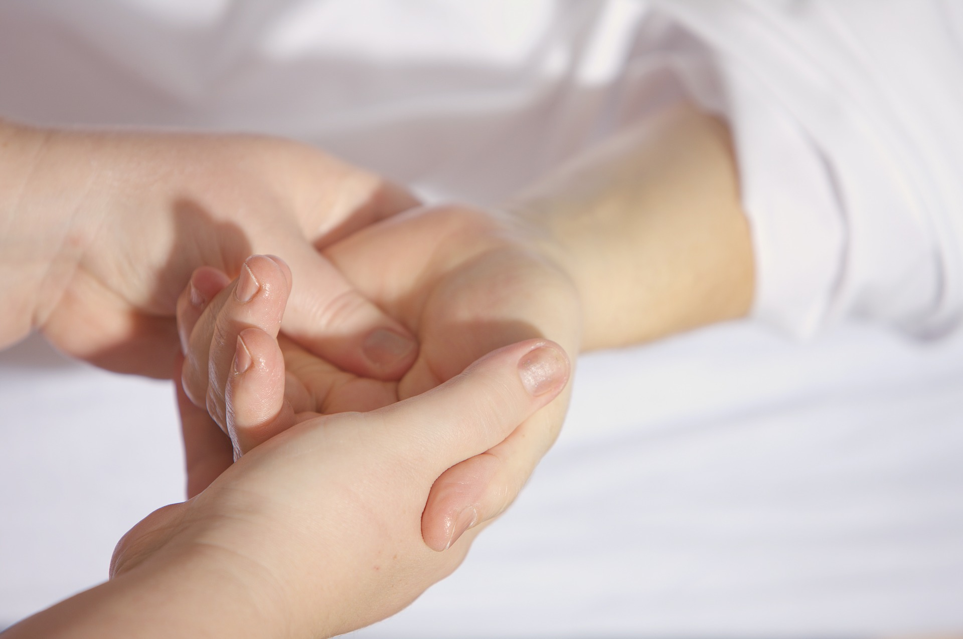 image of acupressure practitioner touching person's hand at pressure point