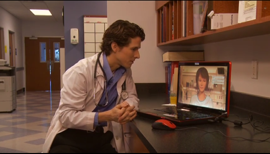 image of doctor in a hospital counseling virtual patient on a laptop screen