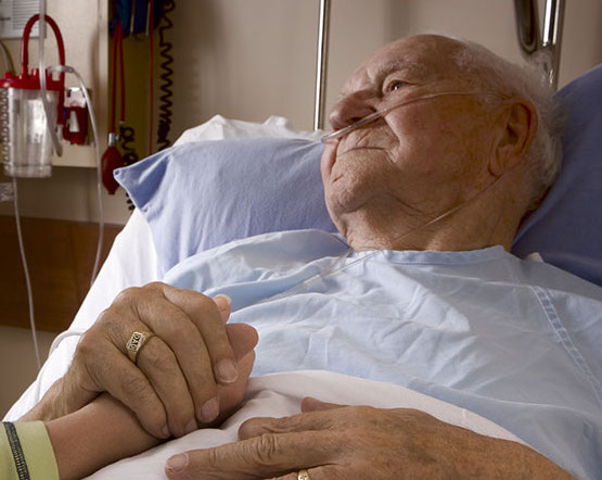 Image of older man in hospital bed holding hand of visitor