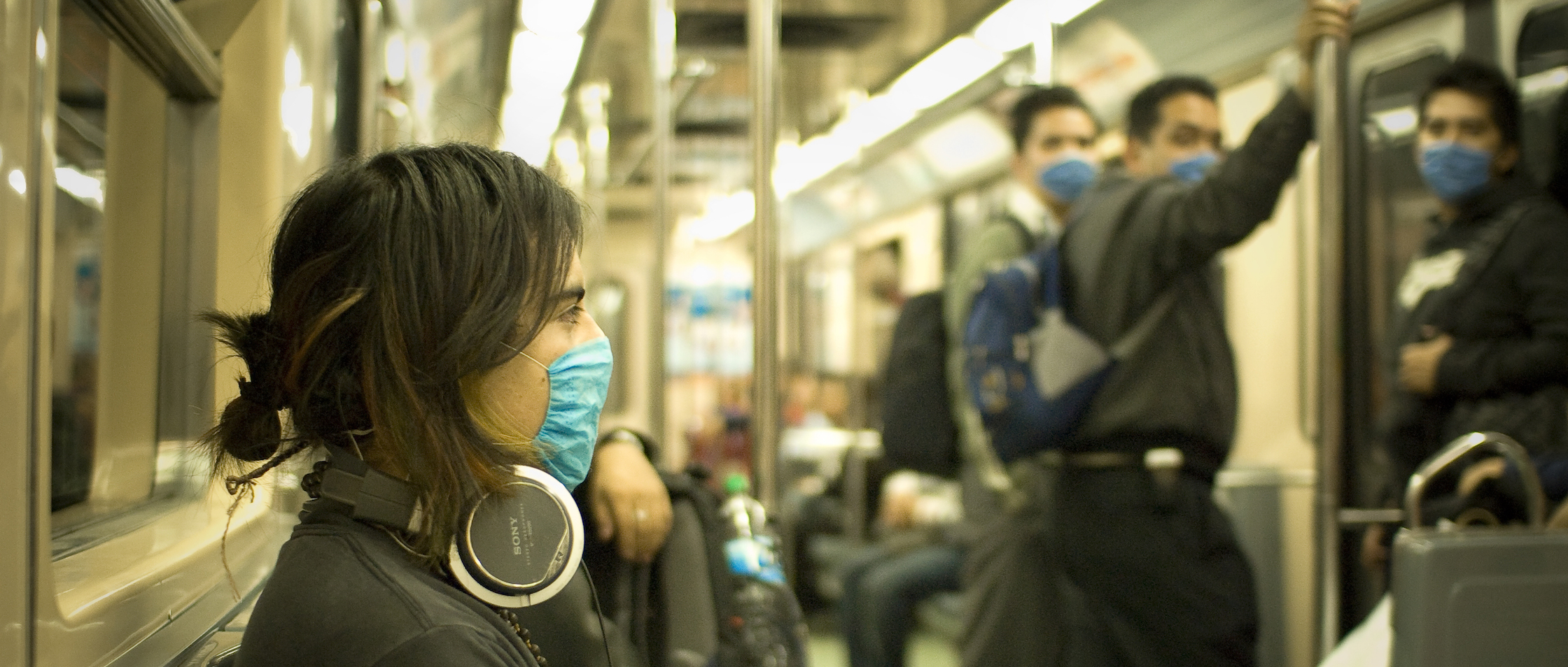 Women and men wearing face masks while riding public transportation