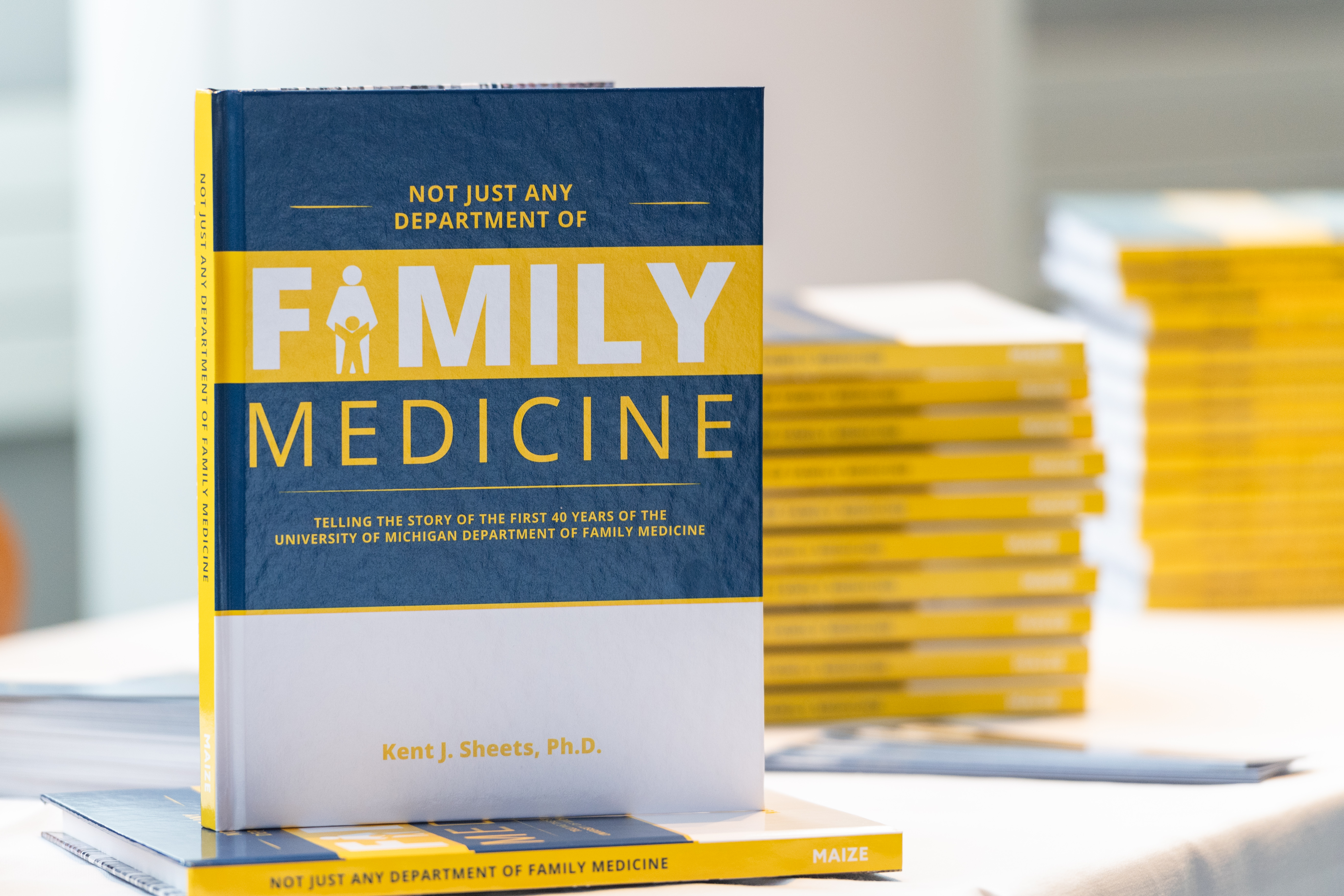 """A book entitled """"Not Just Any Department of Family Medicine"""" standing on top of a stack of the same book."""