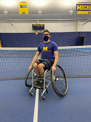 Man wearing a fabric mask in an athletic wheelchair on a tennis court in front of a tennis net.