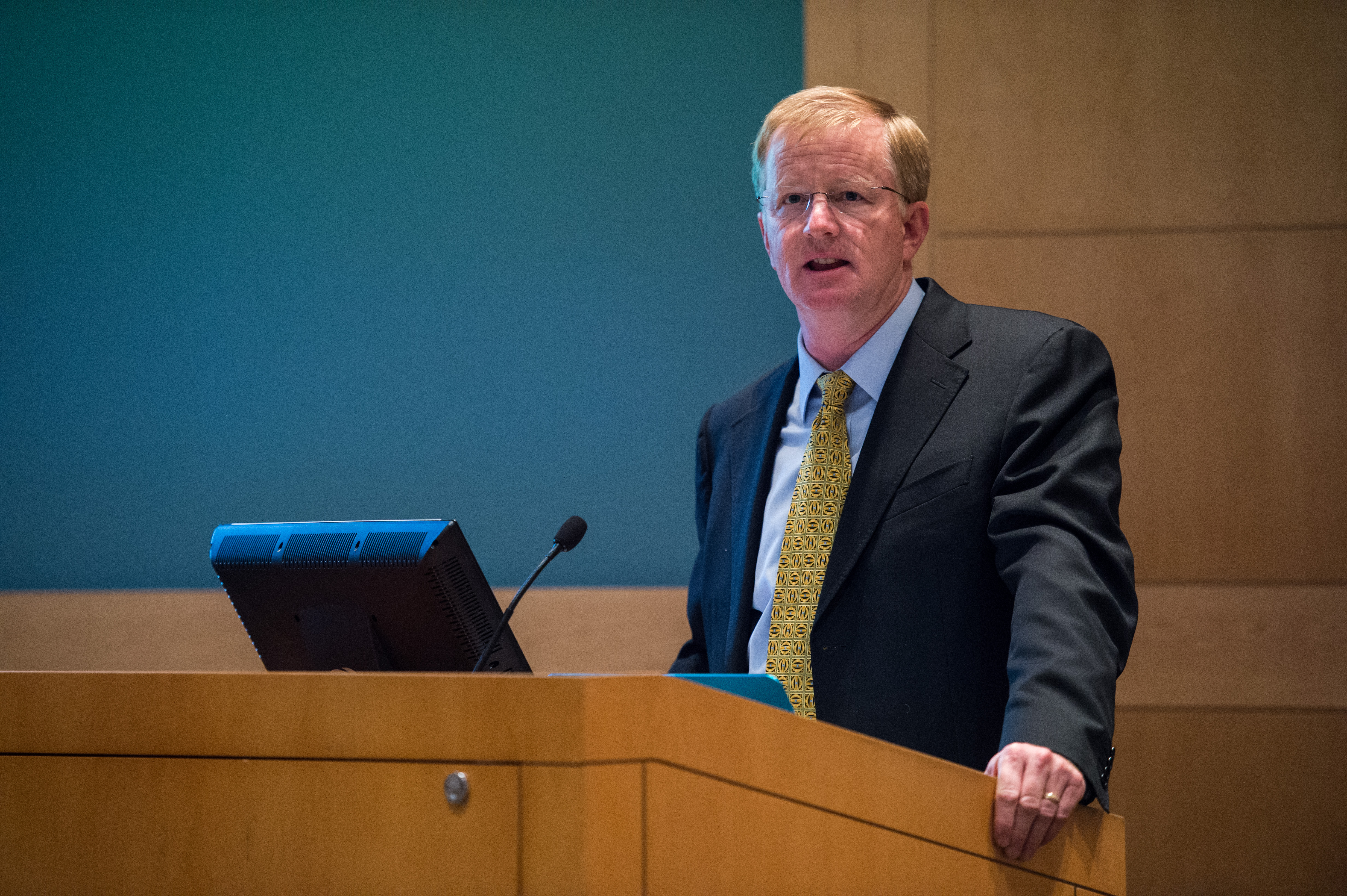 Dr. Brown speaking at a podium during the Dellon Lectureship