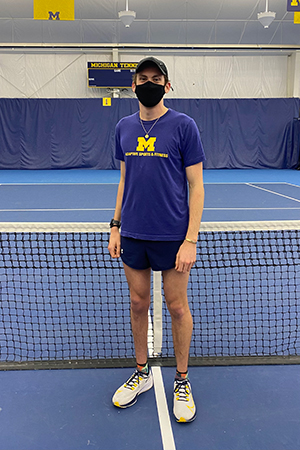 Man wearing a fabric mask stands in front of a tennis net on a tennis court.