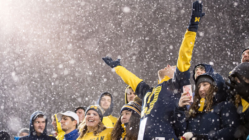 Michigan football fans cheer in the rain