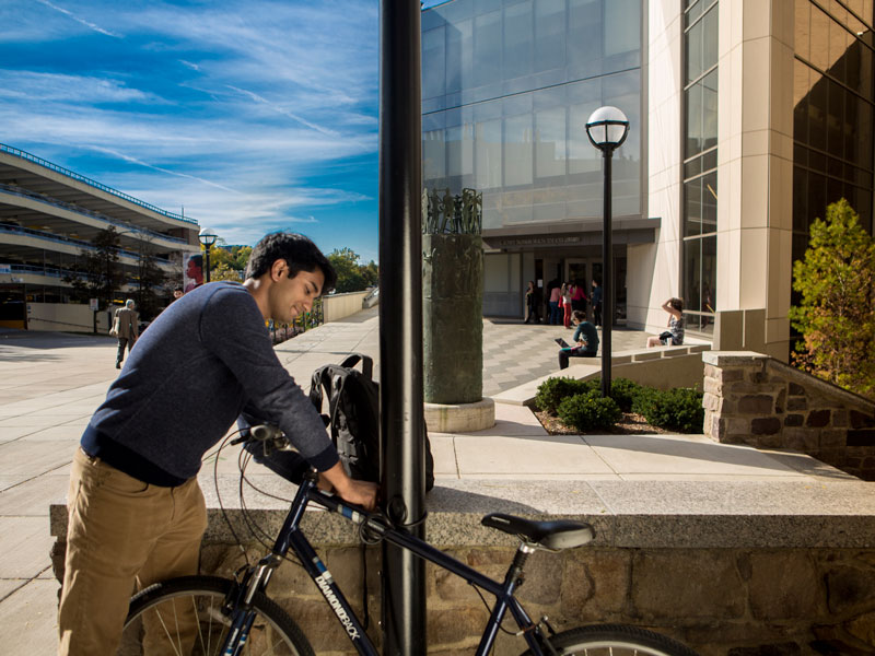 A medical student locks their bike in front of the health sciences library