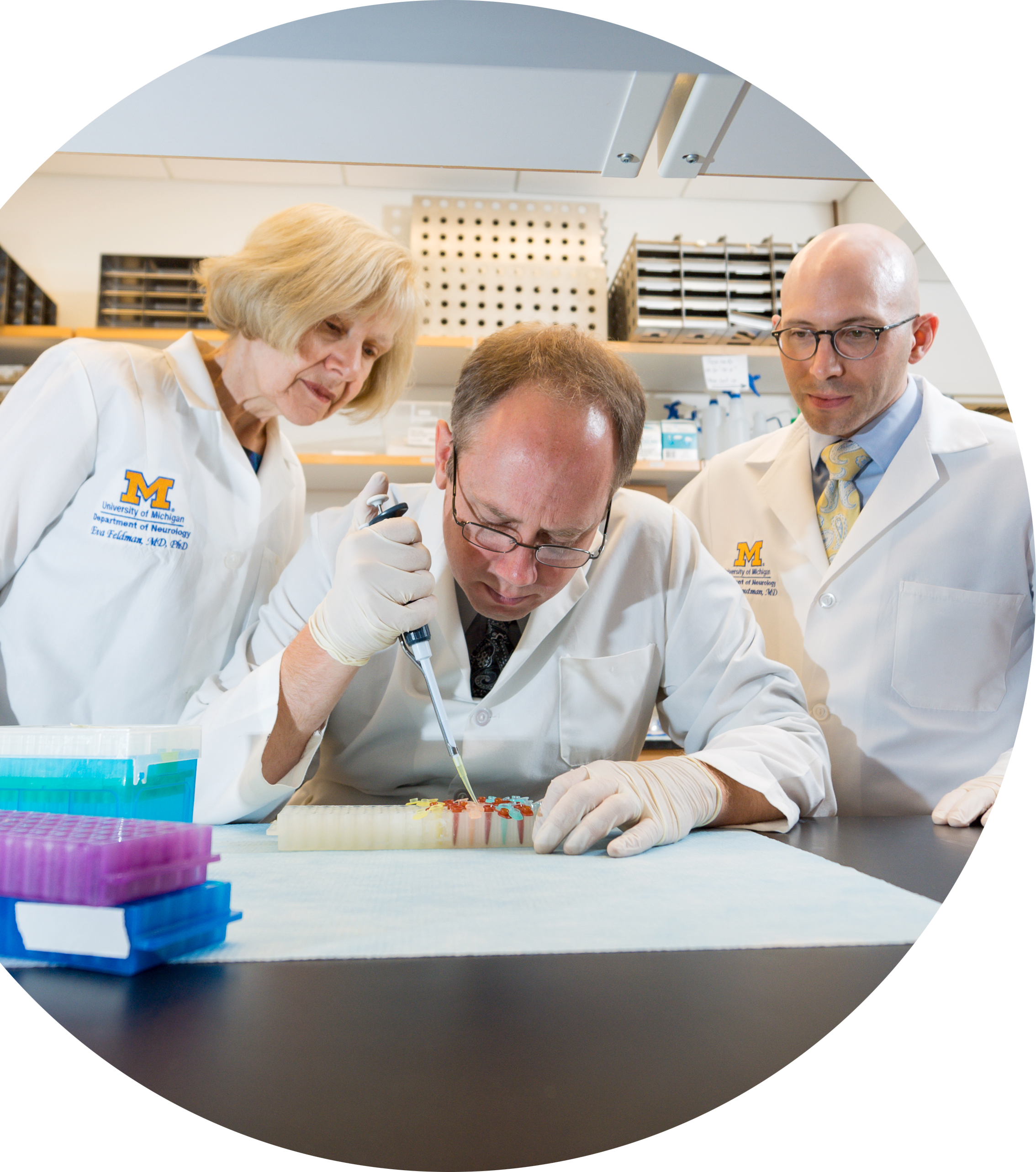 photo of Dr. Eva Feldman, Dr. Benjamin Murdock and Dr. Stephen Goutman working in the lab