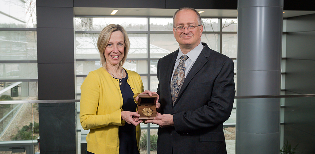 Carol Bradford, M.D., M.S., presents the professorship award to David Antonetti, Ph.D.