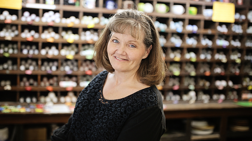 Art store owner Traci Lawson, in front of shelves of art supplies