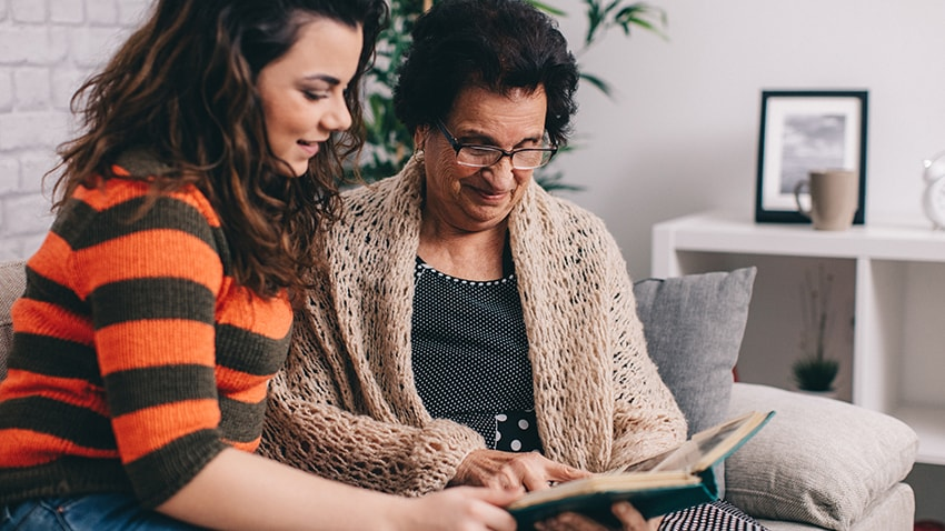 Young woman and older woman looking at a book.
