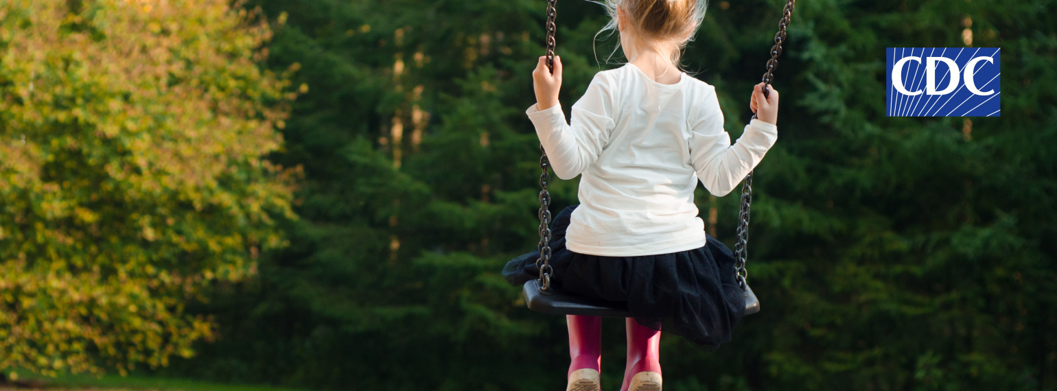 A young female child sits on a swing with her back to the camera. She is surrounded by greenery. The CDC logo appears in the top right-hand corner.
